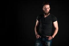 Un hombre carismático y elegante con una barba se coloca integral en un fondo negro Marco horizontal Fotografía de archivo