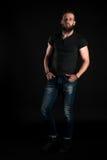 Un hombre carismático y elegante con una barba se coloca integral en un fondo negro Marco vertical Fotografía de archivo