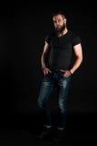 Un hombre carismático y elegante con una barba se coloca integral en un fondo negro Marco vertical Foto de archivo