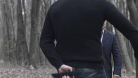 Un hombre caucásico blanco con la capilla amenaza a un hombre en traje con su cuchillo La víctima se defiende con un arma almacen de video