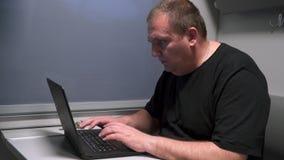 Un hombre cerca de la ventana de un tren m?vil trabaja con un ordenador port?til almacen de metraje de vídeo