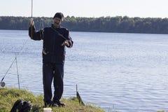 Un hombre cogió un pescado en el cebo imagen de archivo