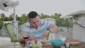 Un hombre come con impaciencia la comida basura en un restaurante metrajes