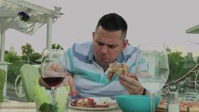 Un hombre come con impaciencia la comida basura en un restaurante almacen de metraje de vídeo