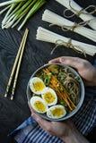 Un hombre come los tallarines del soba del alforf?n con la salsa y los acompa?amientos en caldo Comida japonesa Cocina asi?tica F fotografía de archivo