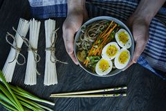 Un hombre come los tallarines del soba del alforf?n con la salsa y los acompa?amientos en caldo Comida japonesa Cocina asi?tica F fotos de archivo