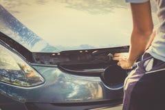 Un hombre con un coche quebrado y él abren el capo fotografía de archivo libre de regalías