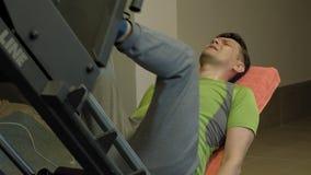 Un hombre con el exceso de peso que hace las prensas de la pierna en el simulador en el gimnasio Hombre de la aptitud training Co metrajes