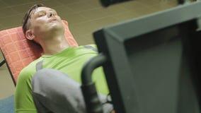 Un hombre con el exceso de peso que hace las prensas de la pierna en el simulador en el gimnasio Hombre de la aptitud training Co almacen de video