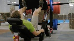Un hombre con el exceso de peso que hace las prensas de la pierna en el simulador en el gimnasio Hombre de la aptitud training Co almacen de metraje de vídeo