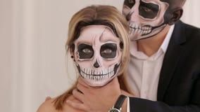 Un hombre con el maquillaje de Halloween está deteniendo a su novia al lado del cuello almacen de metraje de vídeo
