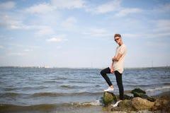 Un hombre con el peinado moderno en ropa casual en piedras en una playa del río Un varón joven que presenta en un fondo natural Imágenes de archivo libres de regalías