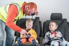 Un hombre con el pelo rojo comprueba su pasaporte Un pequeño niño feliz se está sentando en el cinturón de seguridad del coche El Fotos de archivo libres de regalías
