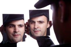 Un hombre, con la cara en el espejo Fotos de archivo