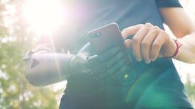 Un hombre con la prótesis moderna de la mano mira su teléfono 4K almacen de video