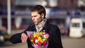 Un hombre con las flores que esperan a su mujer en la ciudad metrajes