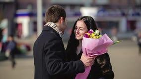 Un hombre con las flores que esperan a su mujer en la ciudad almacen de metraje de vídeo