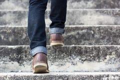 Un hombre con los geans y los zapatos azules de la zapatilla de deporte en escalera Fotos de archivo