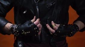 Un hombre con los guantes de cuero claveteados pone y relampaga para arriba su chaqueta de cuero, cierre para arriba almacen de metraje de vídeo
