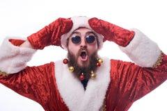 un hombre con los juguetes de la Navidad en una barba y en un traje de Santa Claus lleva a cabo las manos cerca de su cabeza foto de archivo libre de regalías