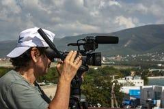 Un hombre con los lanzamientos de una cámara contra la perspectiva de las montañas y del mar foto de archivo