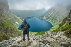 Un hombre con los polos del senderismo que miran el lago en las montañas de Tatra Foto de archivo libre de regalías