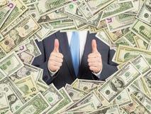 Un hombre con los pulgares para arriba dentro del marco de las cuentas de dólar de EE. UU. Todo el nominal carga en cuenta ambos  Fotos de archivo libres de regalías