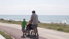 Un hombre con un muchacho lleva una silla de ruedas con su abuela a lo largo de la costa almacen de metraje de vídeo