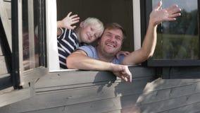 Un hombre con un muchacho rubio dice adiós a las huéspedes de la ventana de una casa de madera en una granja en el verano almacen de metraje de vídeo