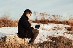 Un hombre con un ordenador portátil en la calle fotos de archivo libres de regalías