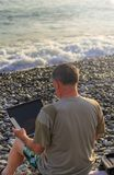 Un hombre con un ordenador portátil que trabaja en la playa imagen de archivo
