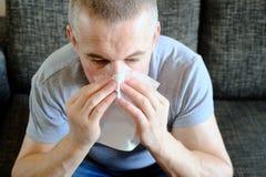 Un hombre con un pañuelo de papel cerca de su nariz Alergias, floraciones de la primavera Reacción al polen, síndrome alérgico fotografía de archivo libre de regalías