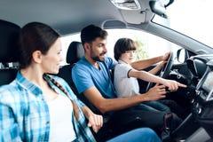 Un hombre con un pequeño hijo se está sentando en la rueda del coche Fotos de archivo libres de regalías