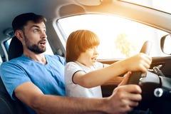 Un hombre con un pequeño hijo se está sentando en la rueda del coche Imagenes de archivo
