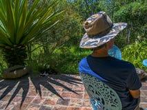 Un hombre con un sombrero que se protege contra el sol del mediodía fotografía de archivo