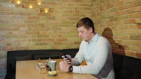 Un hombre con un teléfono se está sentando en un café almacen de metraje de vídeo
