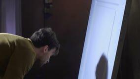 Un hombre con un cepillo, pinta la puerta de madera metrajes