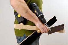 Un hombre con un destornillador y una madera sin cuerda en su mano en una camisa verde foto de archivo