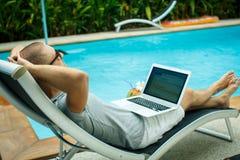Un hombre con un ordenador portátil por la piscina Imagen de archivo libre de regalías