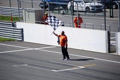 Un hombre con una bandera a cuadros en la raza bikes la pista Imagenes de archivo