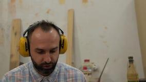 Un hombre con una barba escucha la música en los auriculares y canta metrajes