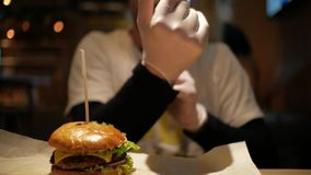 Un hombre con una barba está llevando guantes para comer una hamburguesa cheeseburger metrajes