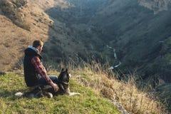 Un hombre con una barba que camina su perro en la naturaleza, colocándose con un contraluz en el sol naciente, echando un resplan Fotografía de archivo