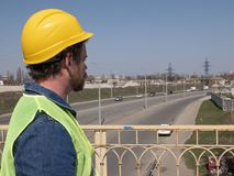 Un hombre con una barba y un bigote en un casco se est? oponiendo en el puente al contexto de la carretera Trabajador del servici fotos de archivo libres de regalías
