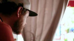 Un hombre con una barba y un casquillo se sienta en un café de la calle y muerde un bocadillo Vista lateral 4K v?deo 4K almacen de video