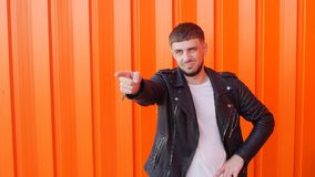 Un hombre con una barba y en una chaqueta de cuero señala su finger en la cámara en un fondo anaranjado, espacio de la copia almacen de video