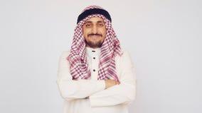 Un hombre con una barba y una sonrisa nacional del vestido Un árabe en una oficina moderna Él dobló sus manos y sonrisas extensam almacen de metraje de vídeo