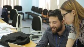 Un hombre con una barba y una mujer del aspecto asiático con los vidrios trabajan juntos en oficina metrajes