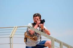 Un hombre con una cámara que se coloca cerca de la cerca imagen de archivo libre de regalías