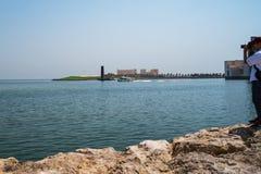 Un hombre con una cámara se coloca en la orilla del océano y mira los edificios de la ciudad de Qatar imagen de archivo libre de regalías